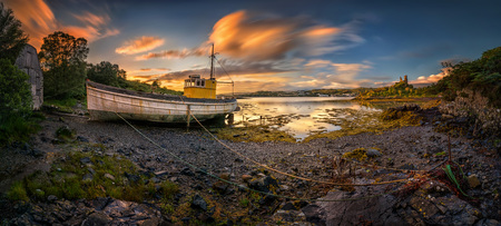 Old boat in old harbour with Kyleakin Castle in background, Isle of Skye, Scotland