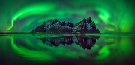 Reflections of aurora borealis around Vestrahorn mountains on Stokksnes black beach, Iceland