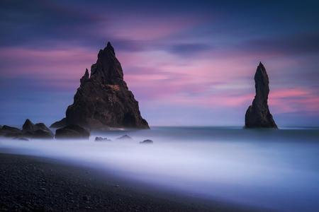 Rocks on black beach Reynisfjara at sunrise, Iceland