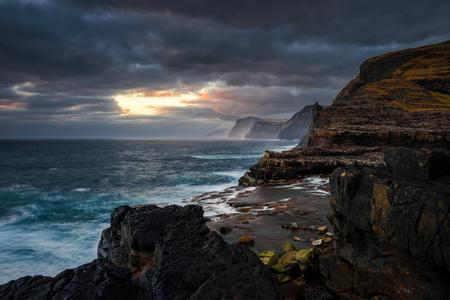 Bosdalafossur waterfall on Vagar island coastline in sunset, Faroe Islands