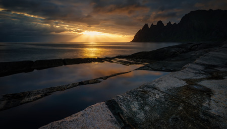 Tugeneset rocky coast with mountains in background at sunset Фото со стока