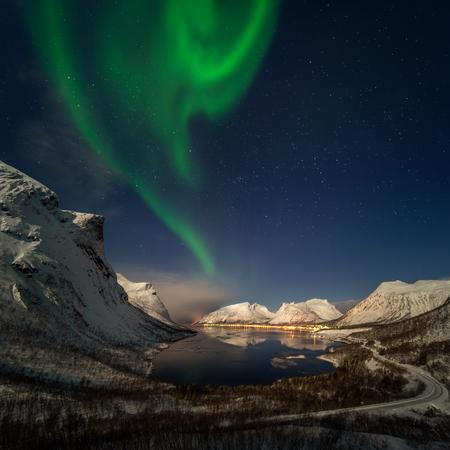Aurora over Bergsbotn fjord among snowy mountains, Senja, Norway Фото со стока