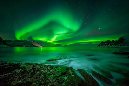 Aurora nad Ersfjord i skalistym wybrzeżem Tugeneset z górami w tle, Norwegia