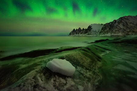 Aurora over Tugeneset rocky coast with Okshornan mountains in background, Norway