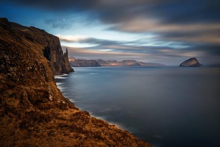 Witch Finger rock and Koltur island in sunset light, Faroe Islands