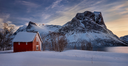 Red cabin in snow at Steinfjorden with frozen mountains in background, Senja, Norway Фото со стока