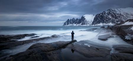 Photographer on Tugeneset rocky coast with Okshornan mountains in background, Senja, Norway