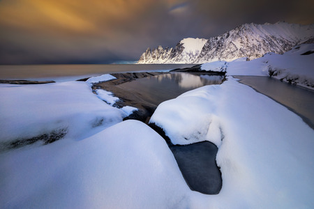 Tugeneset snowy coast with mountains in background at sunset, Norway Фото со стока