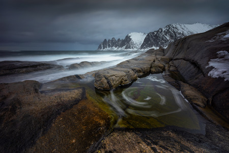 Tugeneset rocky coast with mountains in background in cloudy weather, Norway
