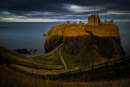 Dunnottar Castle on high cliffs in sunset light, east coast of Scotland