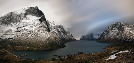 Kirkefjorden village in stormy weather among snowy mountains of Moskenesoya island, Lofoten