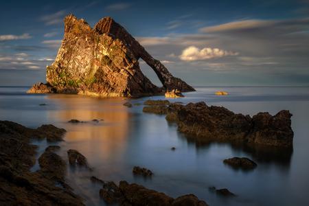 Bow Bow Fiddle Rock reflection in sunset light, Portknockie, Scotland Stockfoto