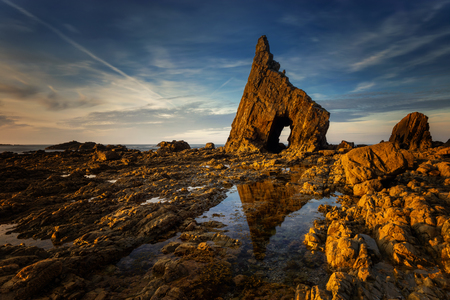Playa de Campiecho rocky coast with the arch at sunset, Asturias, Spain