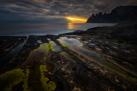 Tugeneset rocky coast with mountains in background at sunset, Norway