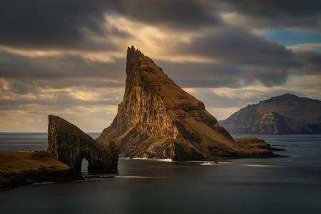 Drangarnir rocky arch on Vagar, Tindholmur and Mykines islands in dusk, Faroe Islands