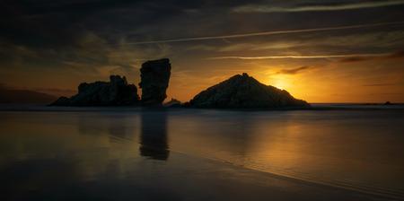 Playa de Bayas rocks at colorful sunset, Asturias, Spain Фото со стока