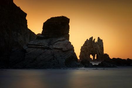 Playa de Portizuelo rocky coast with cliffs in background at sunset, Asturias, Spain