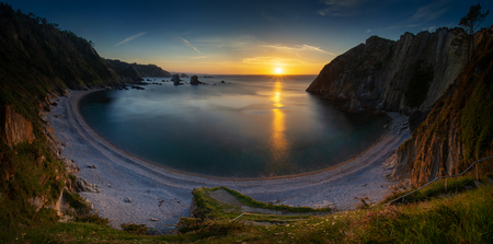 Panorama of Playa del Silencio rocky coast with cliffs in background at sunset, Asturias, Spain Фото со стока