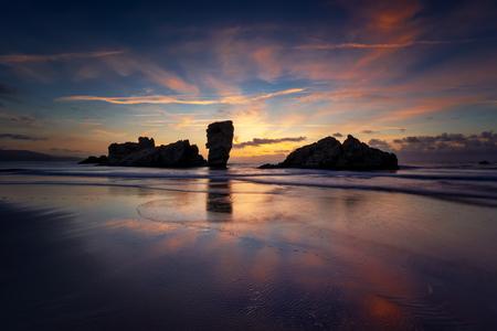 Playa de Requexinos rocks at colorful sunset, Asturias, Spain