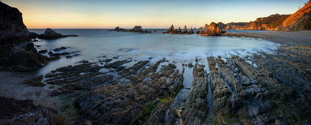 Panorama of Playa de Gueirua rocky coast with cliffs in background at sunset, Asturias, Spain