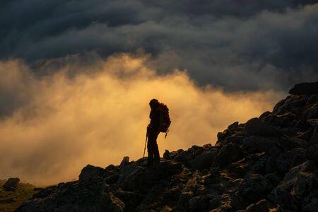 Randonneur sur Breidtinden avec des nuages en arrière-plan au coucher du soleil, Senja, Norvège Banque d'images