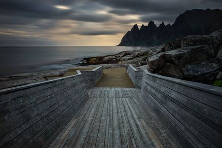 Catwalk on Tugeneset rocky coast with mountains in background at sunset, Norway