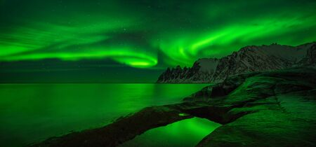 Panorama of aurora over Tugeneset rocky coast with mountains in background, Senja, Norway Фото со стока
