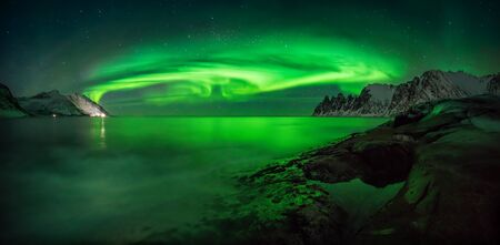 Panorama of aurora over Tugeneset rocky coast with mountains in background, Senja, Norway Banque d'images
