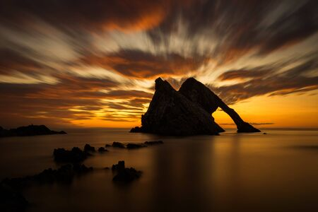 Bow Fiddle Rock reflection in sunrise light, Portknockie, Scotland