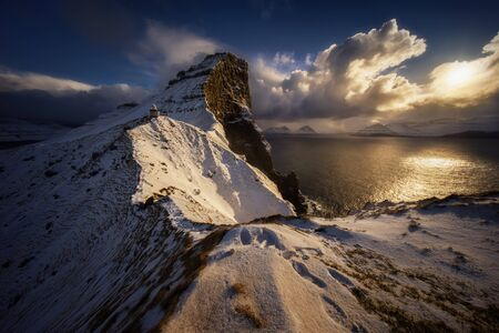Kallur lighthouse on Kalsoy Island with Borgarin mountain behind in winter, Faroe Islands Banque d'images