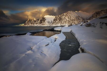 Tugeneset snowy coast with mountains in background at sunset, Norway Banque d'images
