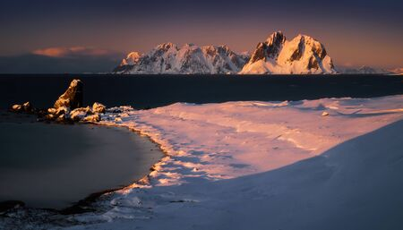 Tuusen Island in snow with Lofoten archipelago in background at sunset, Norway