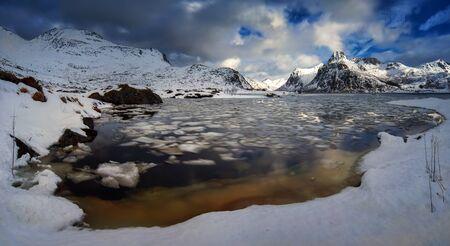 Snowy mountains around Flakstadpollen fjord with icebergs, Flakstadoya, Lofoten  Stockfoto