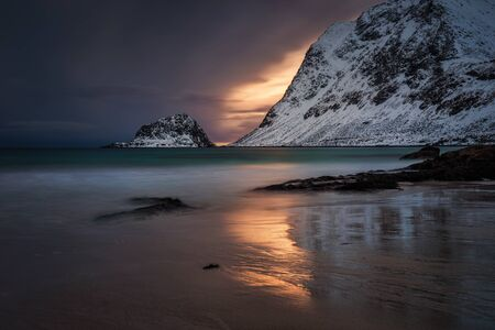 Colorful and moody winter sunset on Haukland Beach, Lofoten