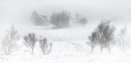 Three cabins in snowstorm in Kilan village on Flakstadoya Island, Lofoten, Norway Stockfoto