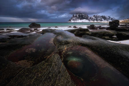 Uttakleiv beach Dragon's Eye with snowy mountains in background at sunset, Norway Stockfoto