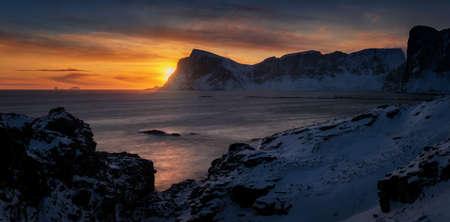 Panorama of Mahornet summit and Vaeroy ridge at orange sunset, Lofoten Norway