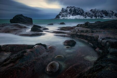Uttakleiv rocky coast with mountains in background at cloudy sunset, Norway