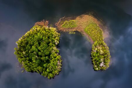 Aerial view of two islands on Gromskie Lake in Mazuras in sunset light, Poland