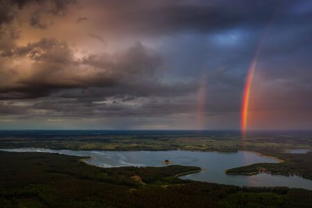 Dramatic clouds and rainbow over Sasek Wielki Lake on Mazuras, Poland