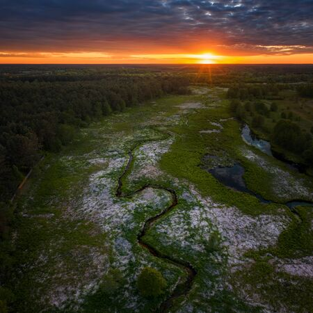 Aerial view of meandering Wymakracz river in sunset light, Poland