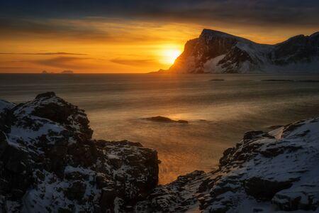 Mahornet summit and Vaeroy ridge at orange sunset, Lofoten Norway