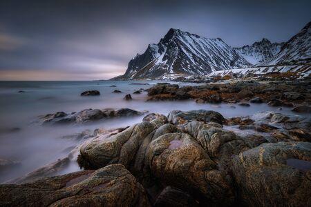 Vikten village coastline with snowy mountains in background, Norway