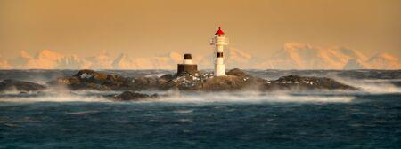 Lighthouse on little island near Vaeroya with mountains in background at sunset, Lofoten Norway