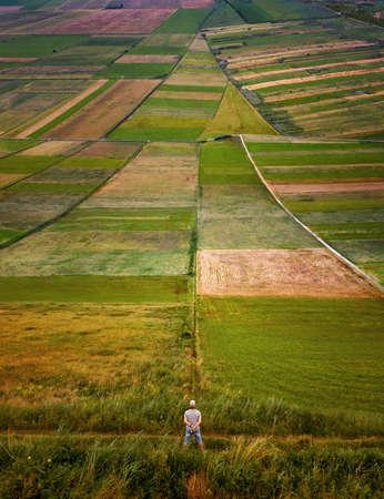 Man on colorful fields in shape of arrow, Kurpie, Poland