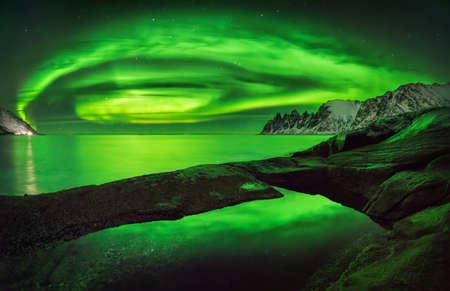 Aurora overTungeneset rocky coast with Okshornan mountains in background, Senja, Norway Stockfoto