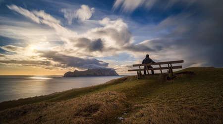 Man on bench at Gasadalur village and Mykines Island in sunset, Faroe Islands Stockfoto