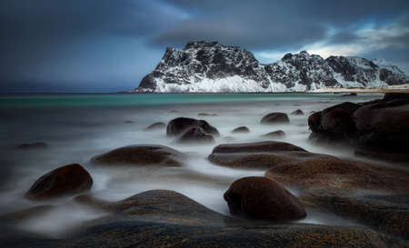 Uttakleiv rocky coast with mountains in background at cloudy sunset, Lofoten, Norway Stockfoto