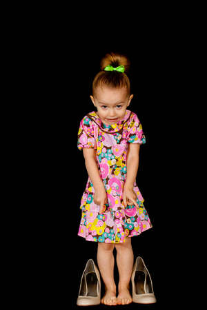A cute girl with big shoes and a black background. Stock Photo - 8644364