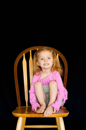 A cute girl sitting on a wooden chair with a black background. photo
